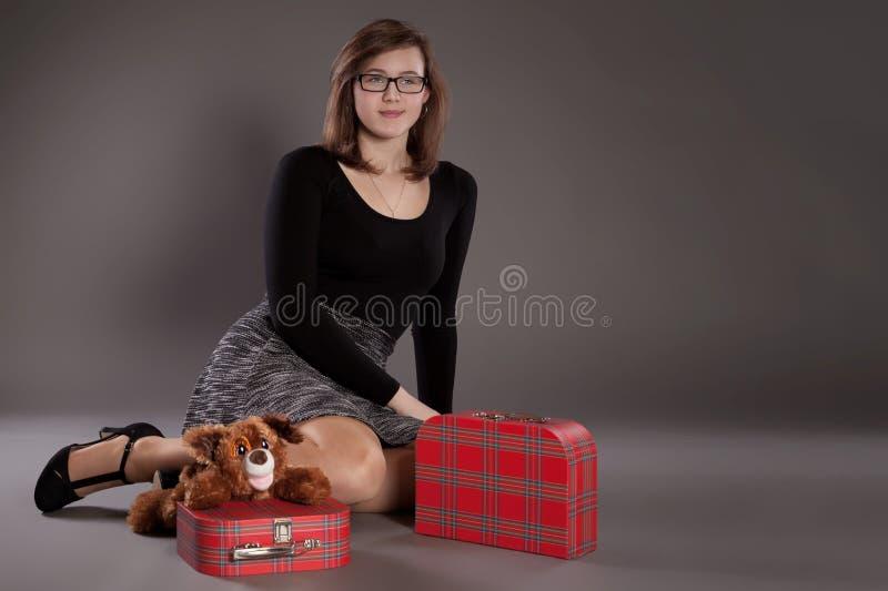 En ung flicka med resväskor och en leksak arkivbilder