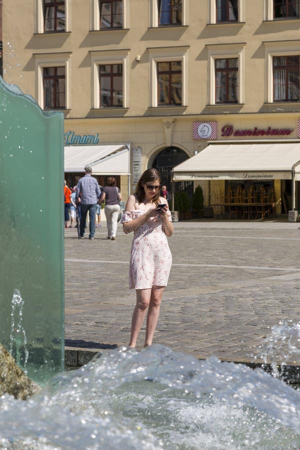 En ung flicka med en smartphone nära springbrunnen på marknadsfyrkanten i Wroclaw, Polen royaltyfri foto