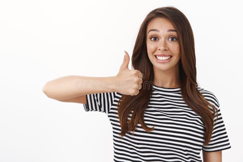 En ung ung flicka med vänligt stöd som leker lyckligt, godkänner ett bra val, visar tummen upp på samma sätt och godkänner skylt royaltyfria bilder