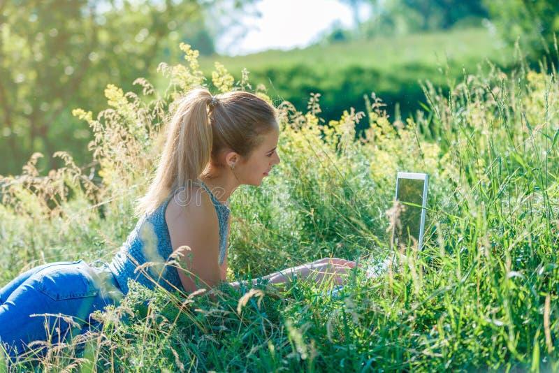 En ung flicka meddelar med hennes älskling till och med en dator i den öppna luften som ligger på det gröna gräset royaltyfri fotografi