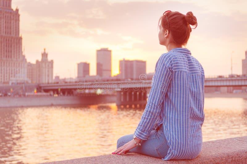 En ung flicka på bakgrunden av cityscapen ser hänsynsfullt in i avståndet royaltyfria foton