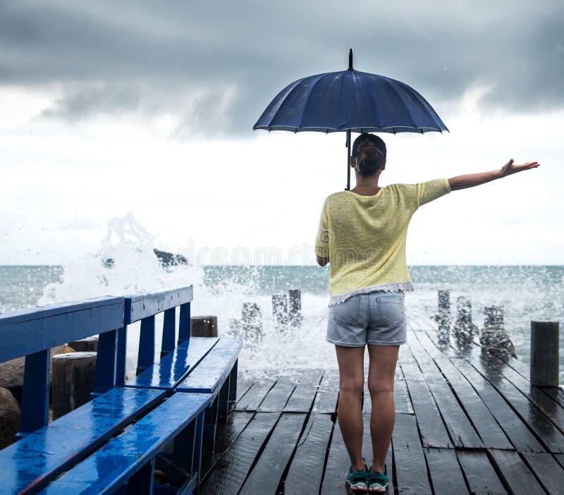 En ung flicka på en pir med ett paraply arkivfoto