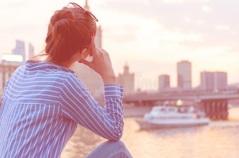 En ung flicka p? bakgrunden av cityscapen ser h?nsynsfullt in i avst?ndet arkivfoton
