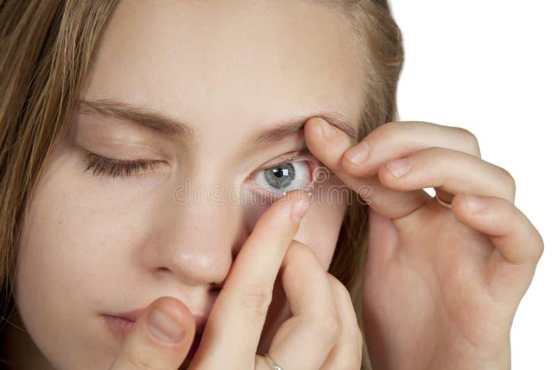 En ung flicka sätter in kontaktlinser in i hennes ögon royaltyfri fotografi