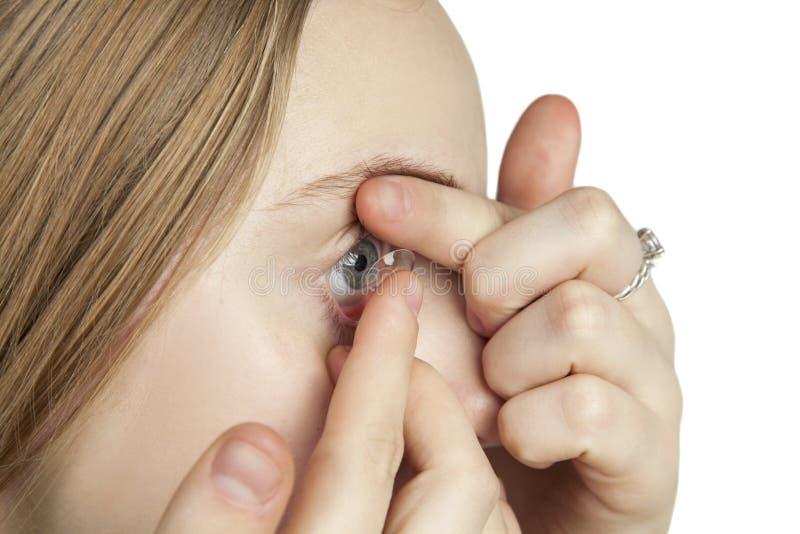 En ung flicka sätter in kontaktlinser arkivbilder