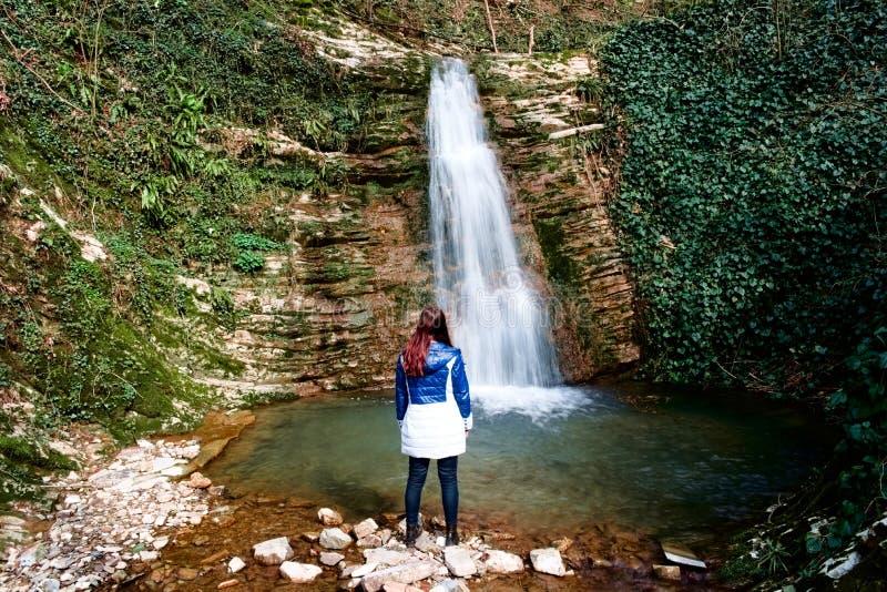 En ung flicka ser vattenfallet royaltyfria bilder