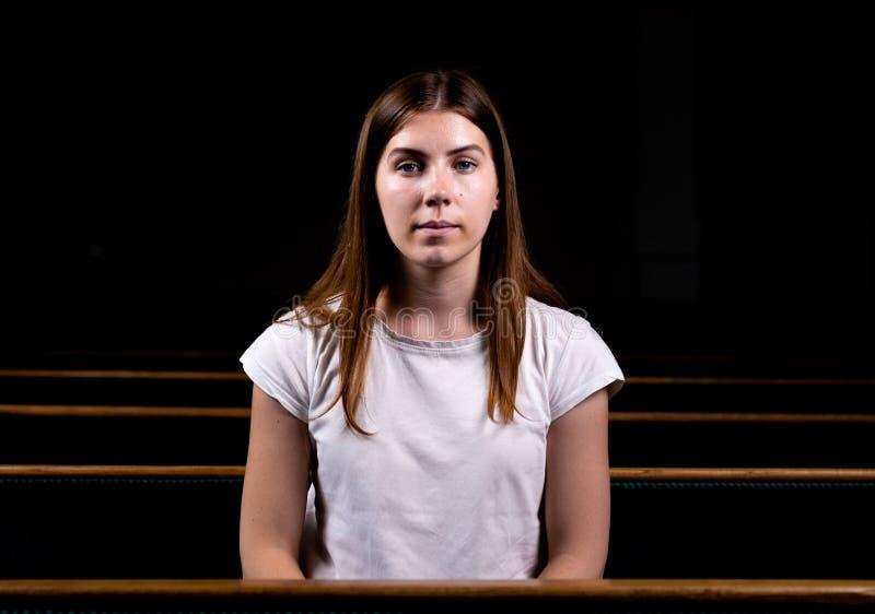 En ung flicka sitter bara i en stor korridor som ser kameran Omkring mörkt arkivfoto