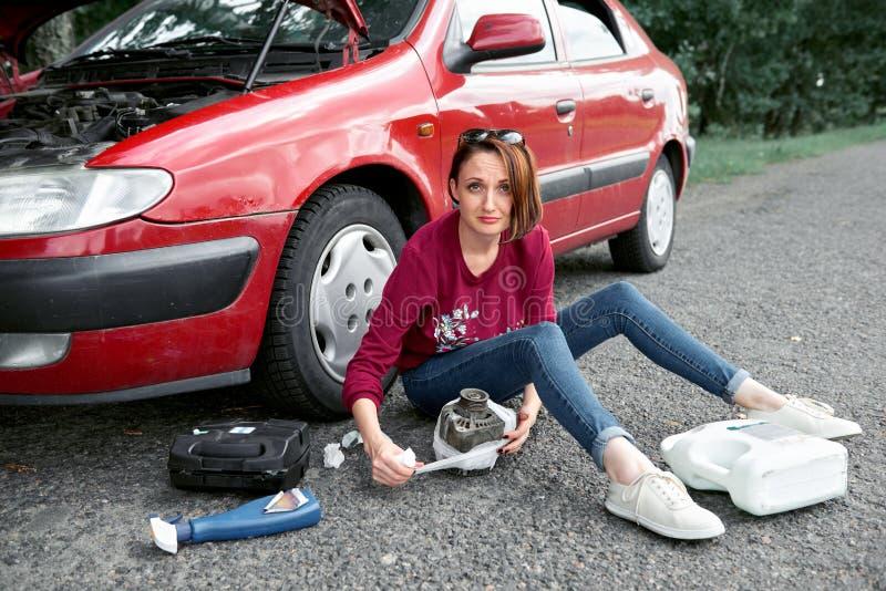 En ung flicka sitter nära en bruten bil och gör reparationer till den elektriska generatorn, bredvid henne där är dåliga delar, h royaltyfri foto