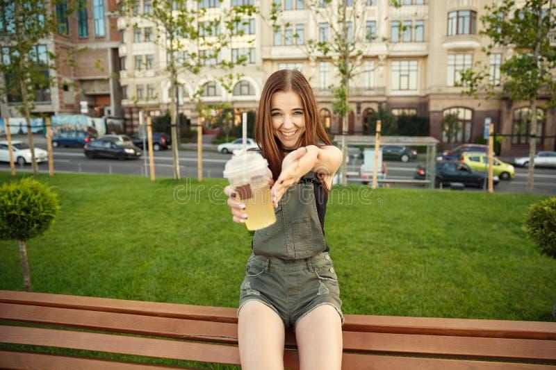 En ung flicka sitter på en bänk i staden, med en drink i hennes mummel fotografering för bildbyråer