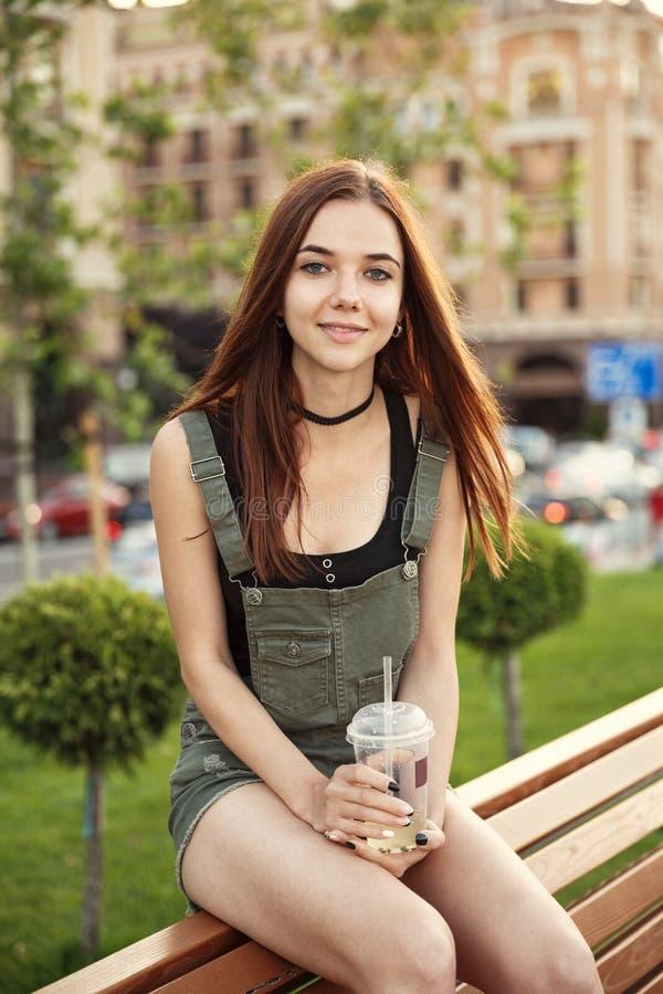 En ung flicka sitter på en bänk i staden, med en drink i hennes mummel royaltyfria foton
