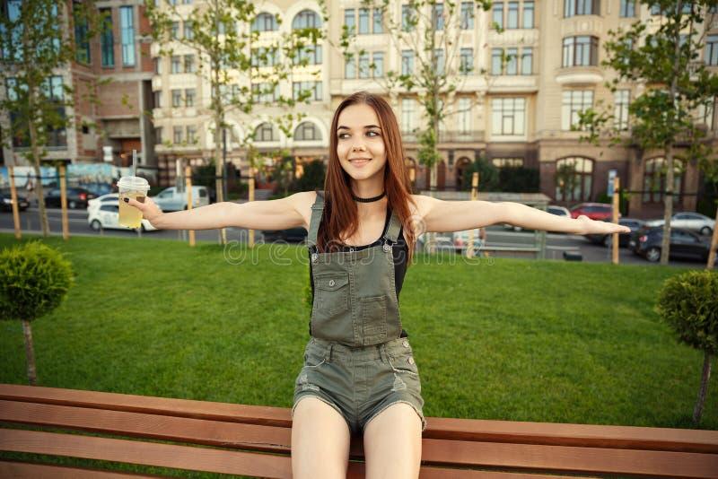 En ung flicka sitter på en bänk i staden, med en drink i hennes mummel arkivbild