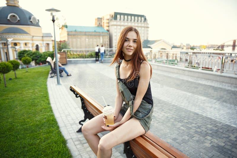 En ung flicka sitter på en bänk i staden, med en drink i hennes mummel arkivfoton