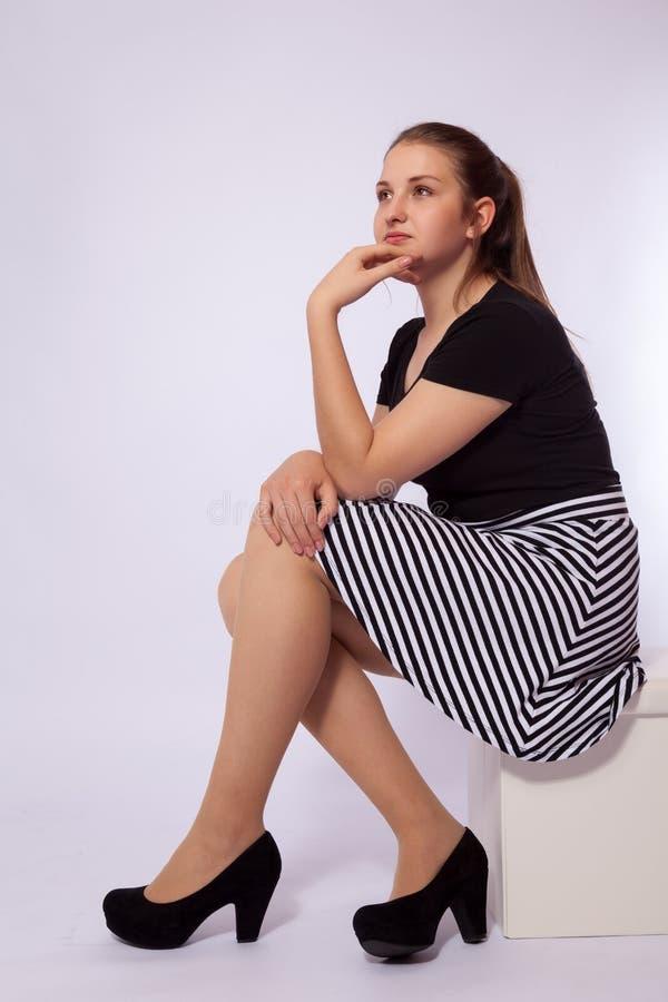 En ung flicka sitter på en stol arkivfoto