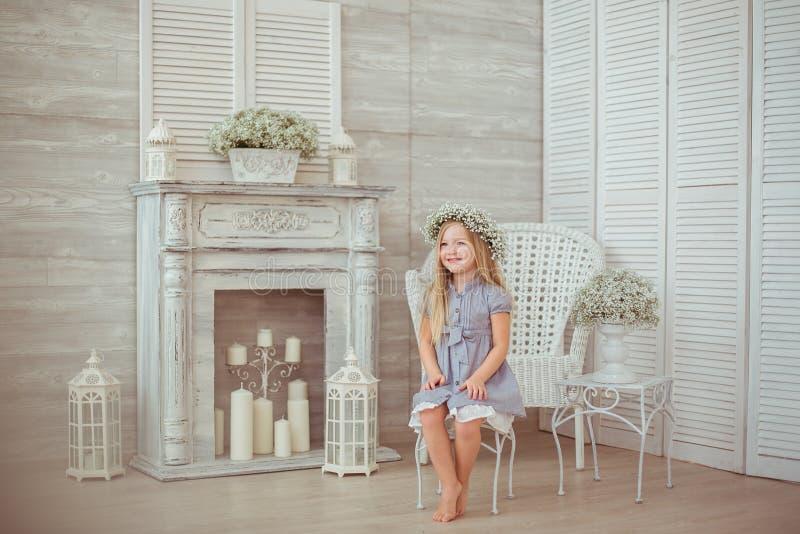 En ung flicka sitter på stolen i rummet royaltyfri foto