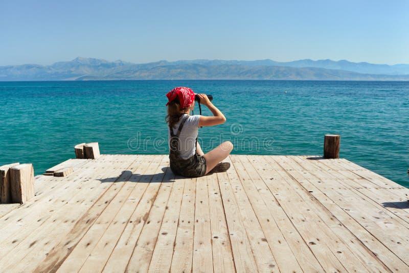 En ung flicka sitter på en träpir och ser till och med kikare royaltyfria foton