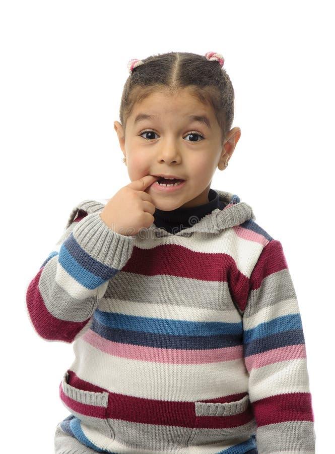 En ung flicka som biter hennes finger arkivfoton