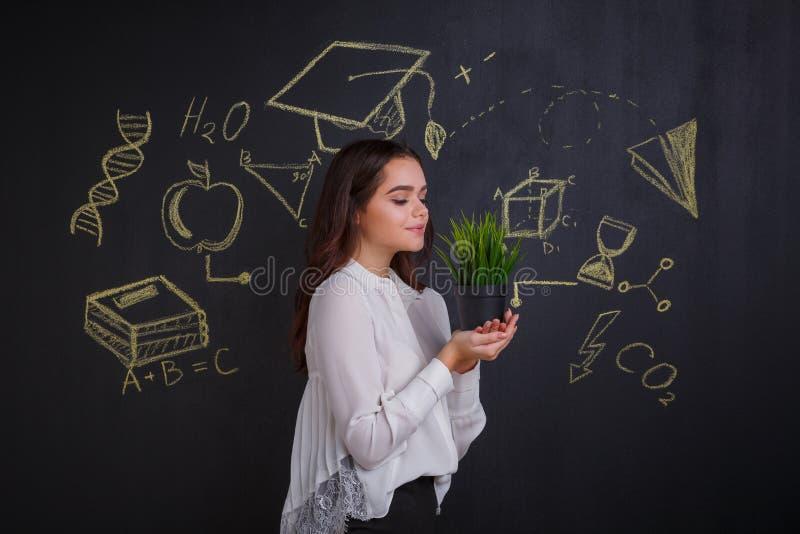 En ung flicka som ser en grön blomma som står vid ett mörkt bräde med tecken av vetenskap och kunskap fotografering för bildbyråer