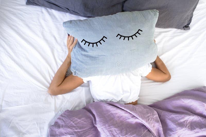 En ung flicka som sover i vit säng, önskar inte att få upp tidigt i morgonen som täcker hennes framsida med kudden med stängda ög arkivfoton