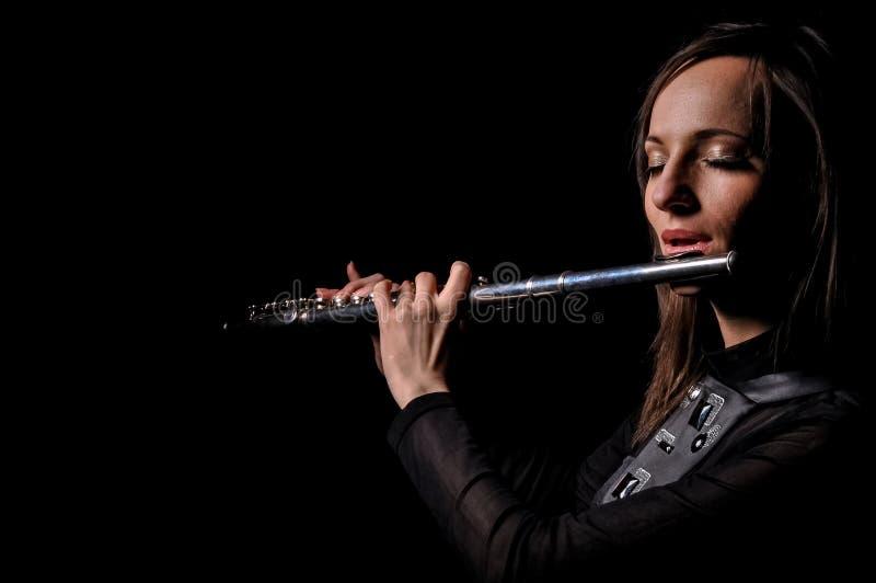 En ung flicka som spelar flöjten royaltyfria bilder