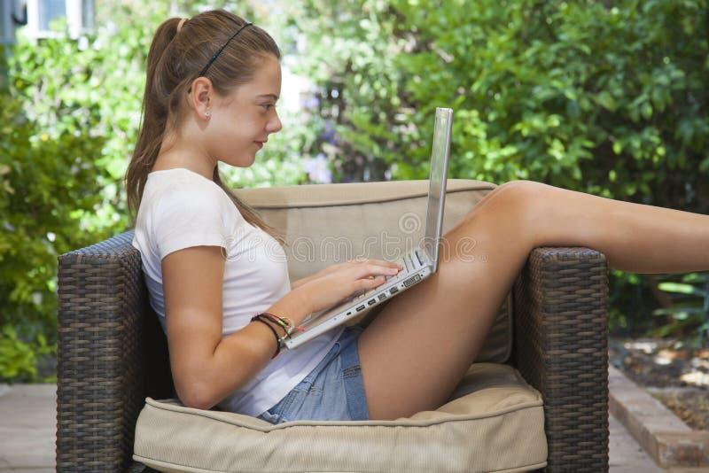 En ung flicka som utanför använder henne bärbar dator arkivbild