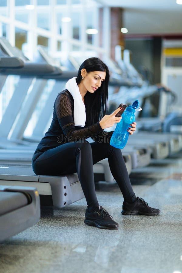 En ung flicka vilar efter en hård genomkörare i idrottshallen royaltyfri fotografi