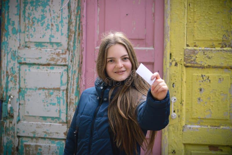 En ung flicka visar en biljett royaltyfri fotografi
