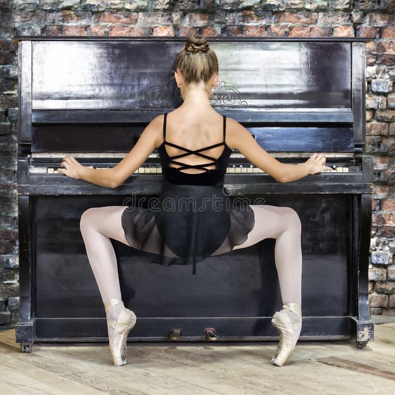 En ung flickabalettdansör spelar det gamla pianot Begreppsmusik, kreativitet fotografering för bildbyråer