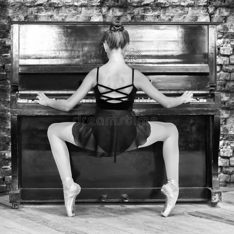 En ung flickabalettdansör spelar det gamla pianot Begreppsmusik, kreativitet tätt foto för black upp white arkivfoto