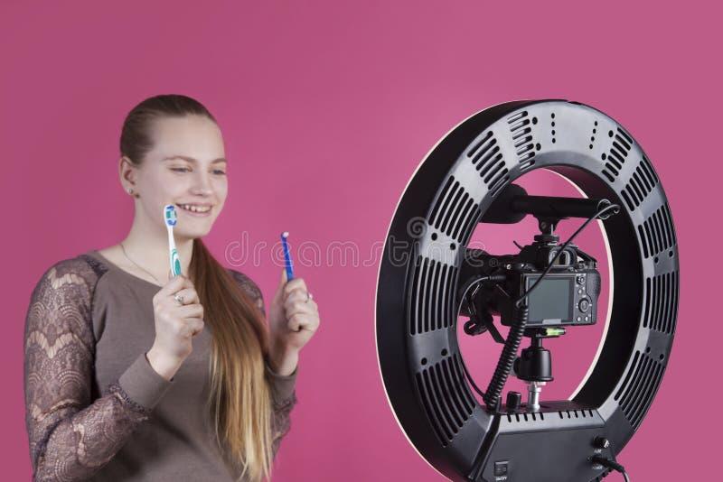 En ung flickablogger har att posera på kameran med tandborstar i hennes händer arkivbild