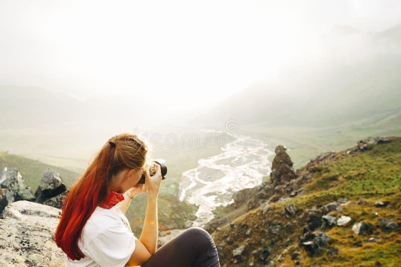 En ung flickahandelsresande tar bilder av en sommarberglandsc royaltyfri fotografi