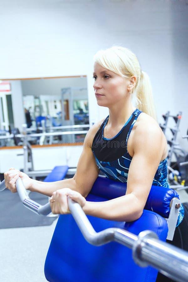En ung flickaidrottsman nen med blont hår utför en övning med en krökt stång i idrottshallen arkivfoto