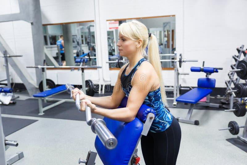 En ung flickaidrottsman nen med blont hår utför en övning med en krökt stång i idrottshallen arkivbilder