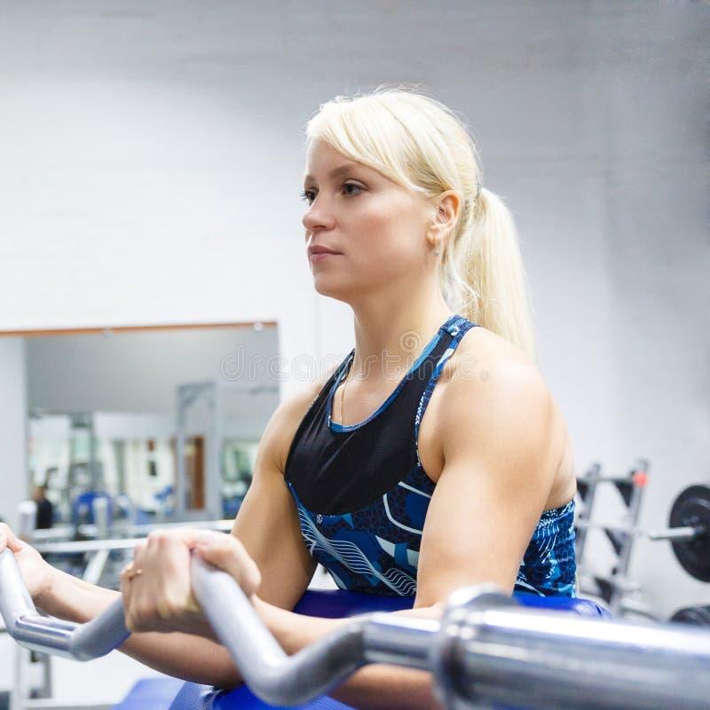 En ung flickaidrottsman nen med blont hår utför en övning med en krökt stång i idrottshallen royaltyfria bilder