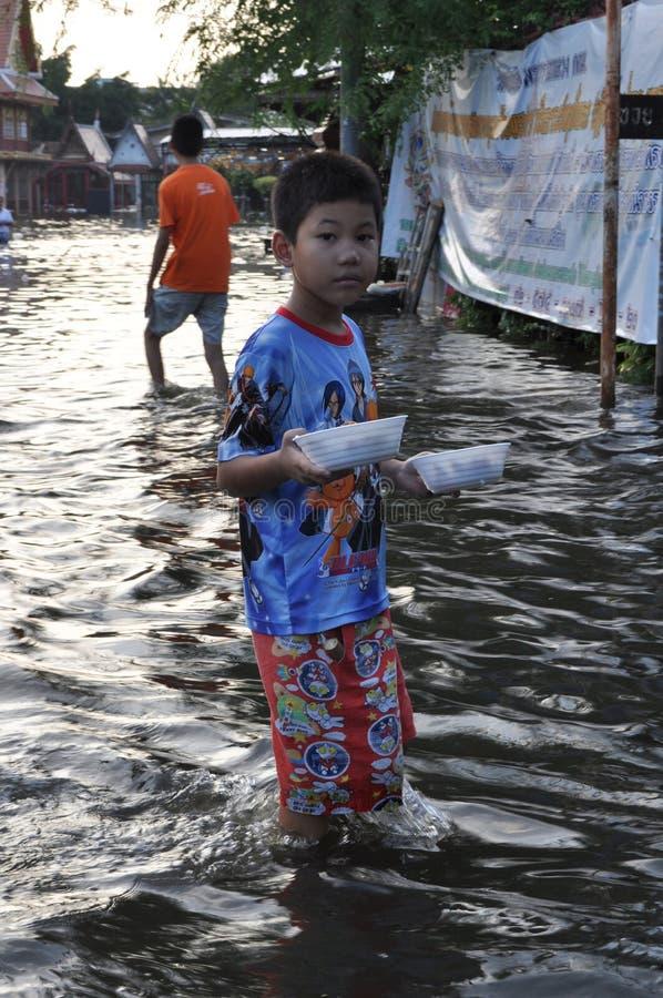 En ung flyktingpojke kommer med mat i en översvämmad gata av Bangkok, Thailand, på 31 Oktober 2011 royaltyfria foton