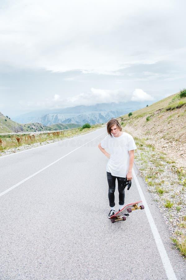 En ung grabb - ett skateboradåkareanseende i förväntan av ett lopp på en landsväg royaltyfri bild