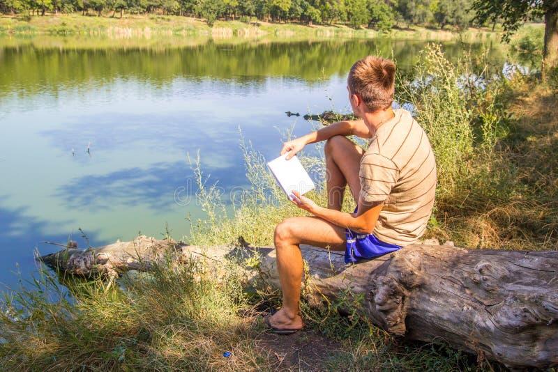 En ung grabb, med en anteckningsbok på bankerna av floden, sjön, sommar tänker rekord i tankar för en anteckningsbok, sol för lan royaltyfri foto