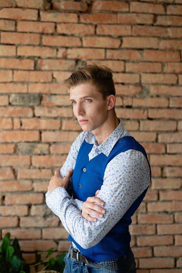 En ung grabb står mot en tegelstenvägg och ser framåtriktat hänsynsfullt royaltyfri bild