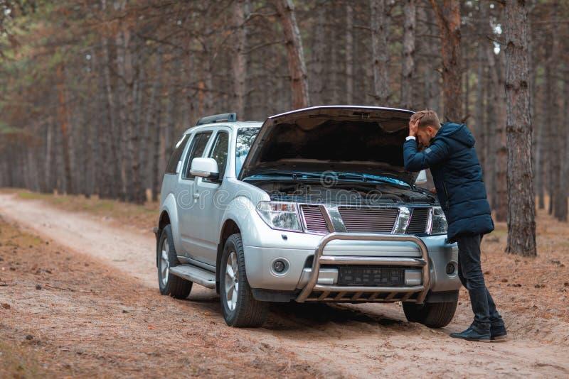 En ung grabb står nära en bruten bil med en öppen huv och rymmer bak huvudet i höstskogen arkivbild