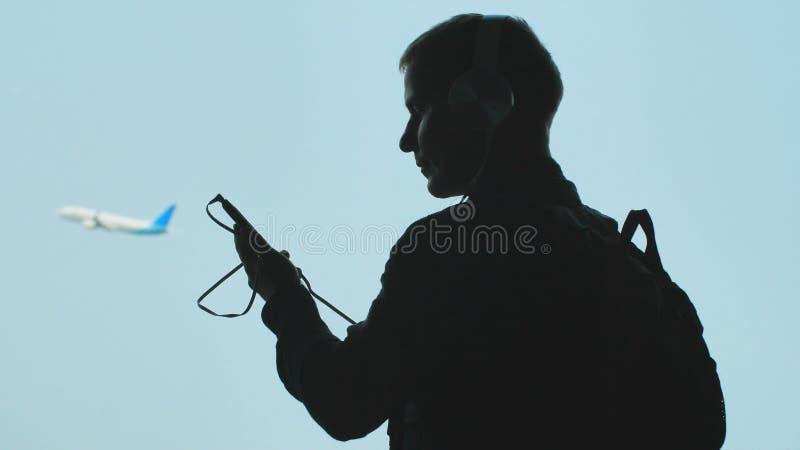 En ung grabb v?nder p? musik p? en smartphone och s?tter p? h?rlurar mot bakgrunden av en niv? som tar av arkivfoto