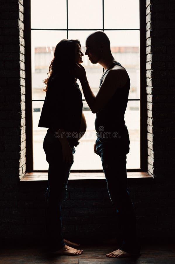 En ung gravid kvinna står med hennes make nära fönstret i studion royaltyfri foto