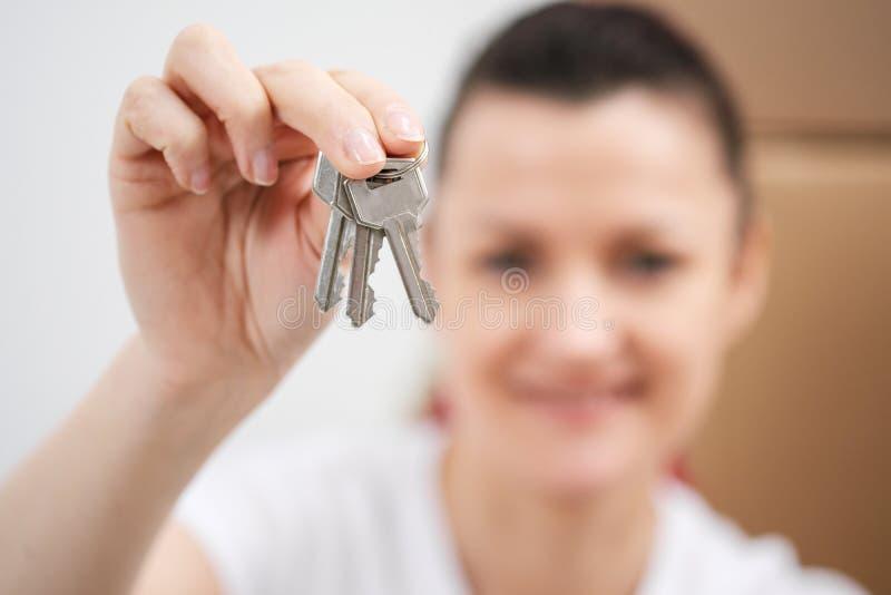 En ung härlig brunettflicka i en vit T-tröja rymmer i hennes händer tangenterna till ett nytt hem, mot bakgrunden av royaltyfria bilder
