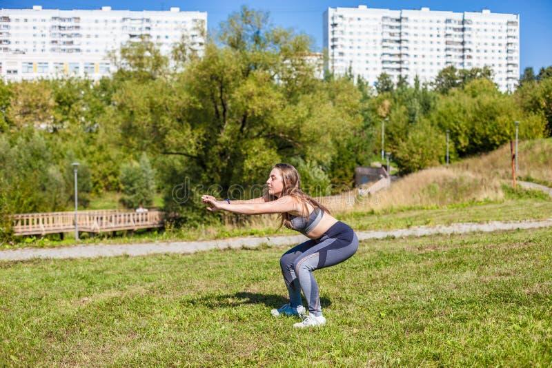 En ung härlig flicka i en grå t-skjorta, grå färg flåsar, och gymnastikskor som gör sportar, övar på det gröna gräset och lyfter  arkivfoton