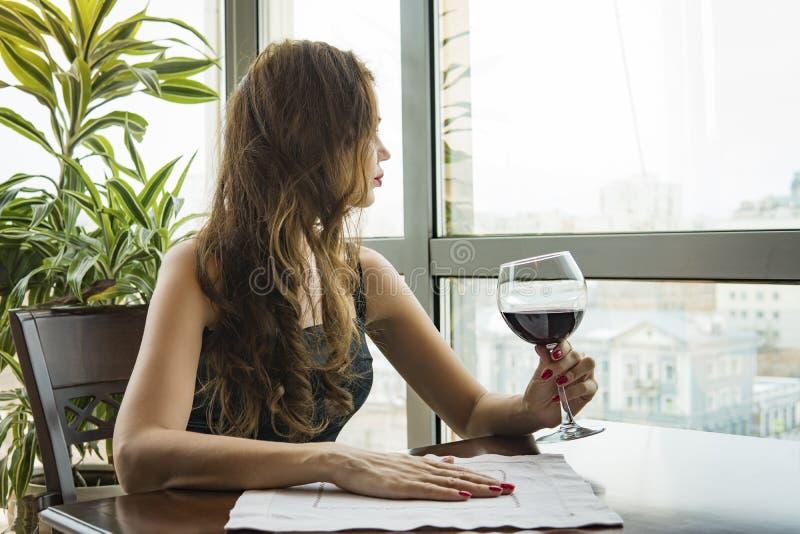 En ung härlig flicka i en svart klänning sitter i en restaurang och dricker vin från ett exponeringsglas nära upp av den unga kvi royaltyfria bilder
