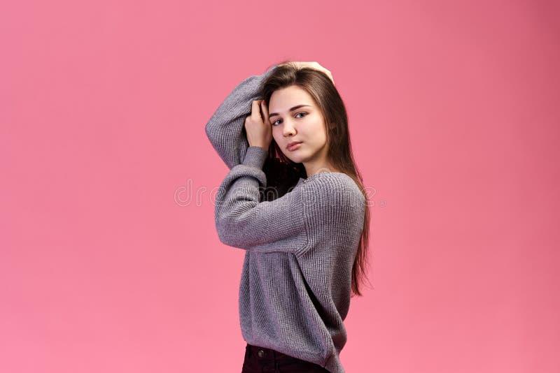 En ung härlig flicka med långt brunn-ansat hår med ett grått omslag ser kameran och står på isolerad rosa bakgrund royaltyfri foto