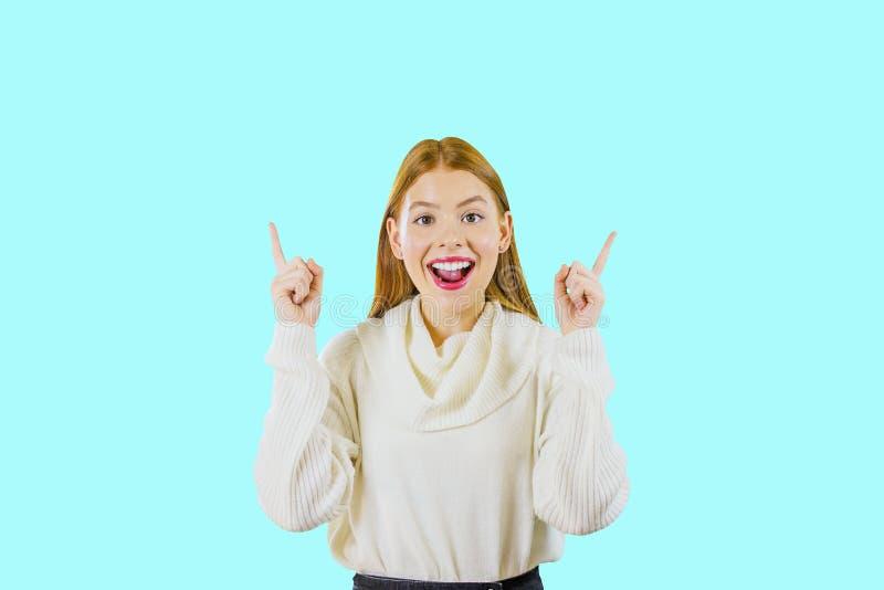 En ung härlig flicka med långt rött hår lyftte upp två pekfingrar och leenden med hennes breda öppna se för mun fotografering för bildbyråer