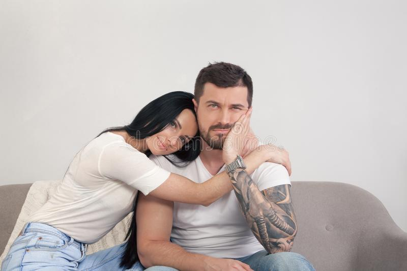 En ung härlig flicka tröstar hennes pojkvän som är att sitta som är besviket Han förlorade hans jobb och är ledsen arkivbilder