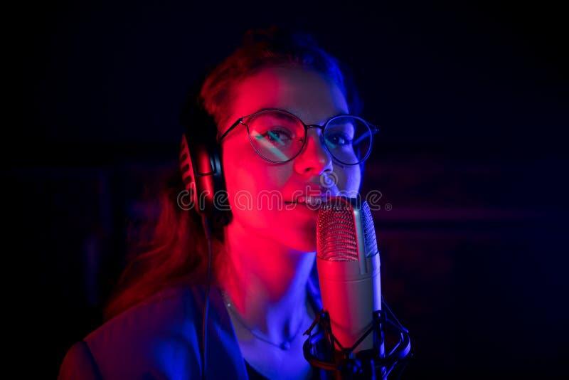 En ung härlig kvinna i exponeringsglas som sjunger vid mikrofonen i neonbelysning arkivbilder