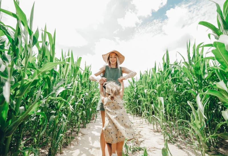 En ung härlig moder med hennes lilla gulliga dotter som har gyckel i havrefältet Natur i landet arkivfoto