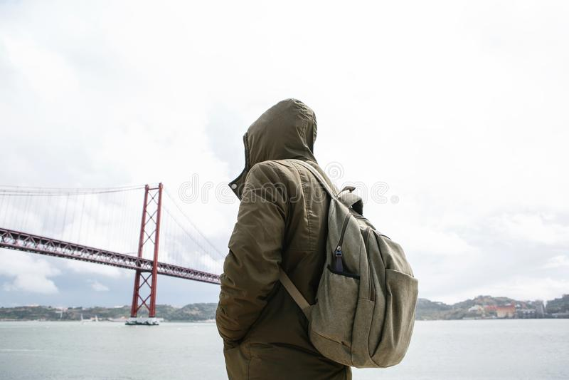 En ung handelsresande eller en turist med en ryggsäck på stranden i Lissabon i Portugal bredvid 25th av April Bridge royaltyfri fotografi