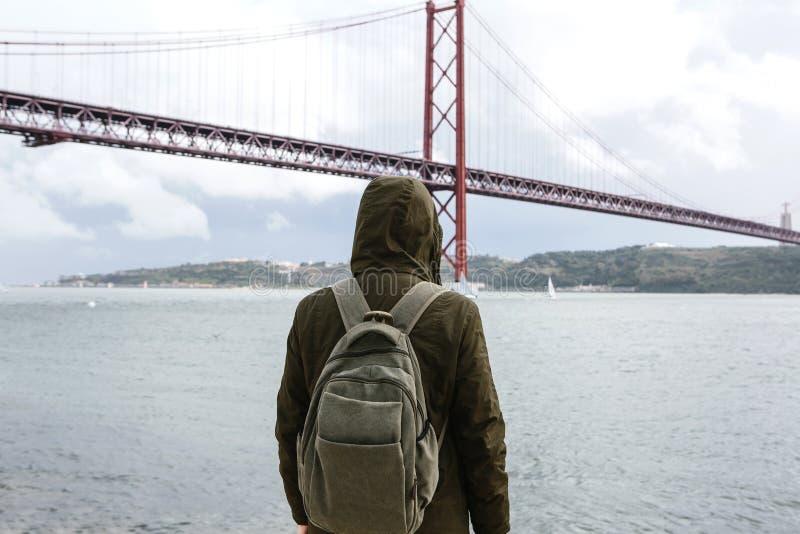 En ung handelsresande eller en turist med en ryggsäck på stranden i Lissabon i Portugal bredvid 25th av April Bridge arkivbild